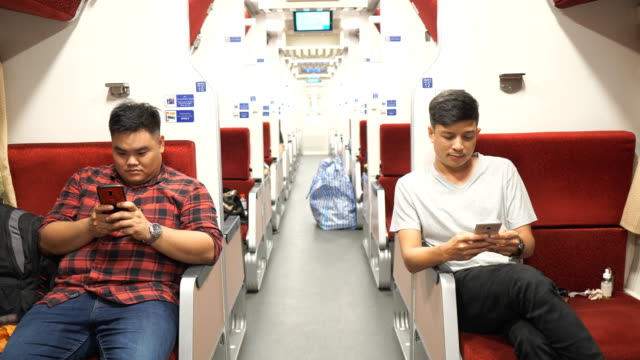 Tow Asian mans enjoy using mobile smartphone in train video