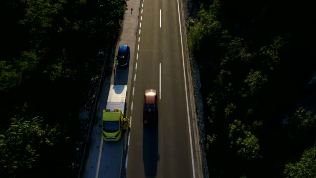 Tow truck help 4k One woman, her car has broken, tow truck is came for help, aerial view, 4k resolution. towing stock videos & royalty-free footage