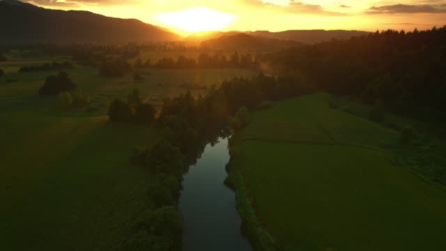 AERIAL Towards the sun rising above the meadows with a river running across them