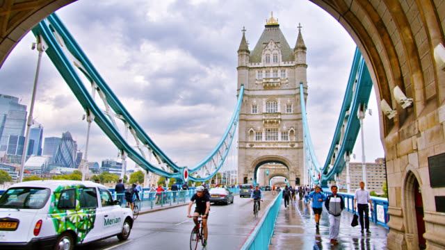 tower bridge in london. bikers, cars, pedestrians enjoy day - london bridge inghilterra video stock e b–roll