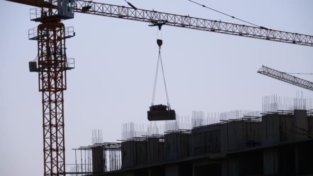 vídeos de stock, filmes e b-roll de o guindaste da torre em um canteiro de obras levanta uma carga no edifício do arranha-céus - pesado peso
