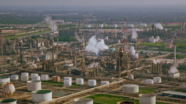 AERIAL Towers of an oil refinery in Texas emitting plumes of smoke video