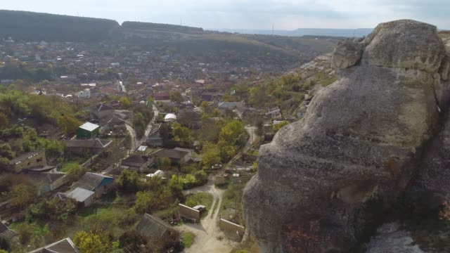 Town located in a natural canyon near a cliff with trees and plants. Shot. Aerial view from the hill