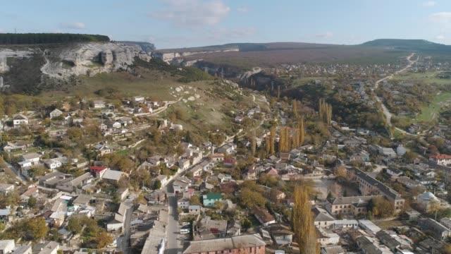 Town near the cliffs against blue sky. Shot. Aerial view video
