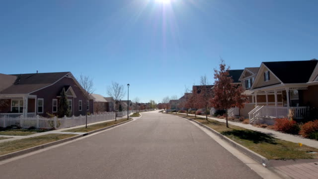 vídeos de stock e filmes b-roll de fpv: townhouses with white picket fences in idyllic suburban city in sunny fall - suburbano