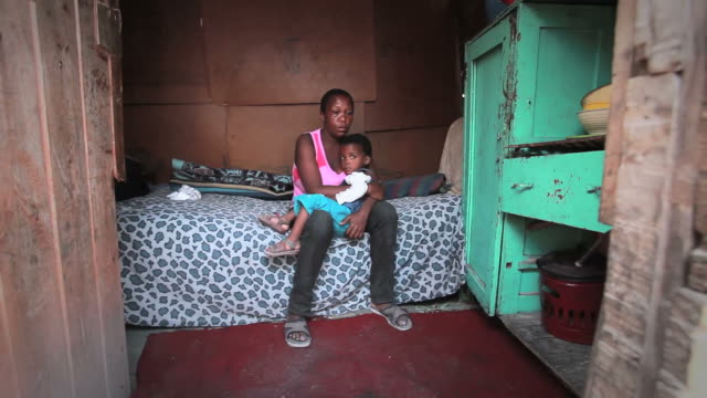 Township Woman with Child A poor African township woman sits on the bed of her single roomed shack in a South African township poverty stock videos & royalty-free footage