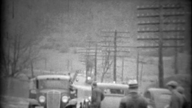 1936: Townspeople helping car get across water flooded road. video