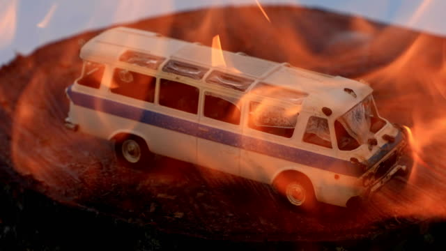 toy bus melts under a stream of fire close up