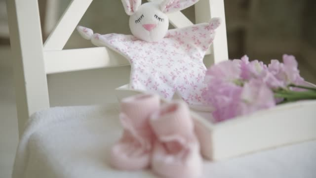 Toy for the newborn hare on the background of knitted pink bootees. Gift for the newborn Toy for the newborn hare on the background of knitted pink bootees. Gift for the newborn baby booties stock videos & royalty-free footage