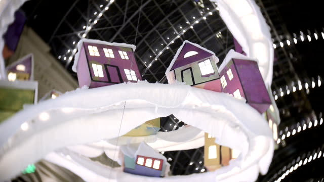 stockvideo's en b-roll-footage met speelgoed huis voor nieuwjaar en kerst decoraties in de winkelcentra, in het centrale deel. decoraties hangen plafond - christmas tree