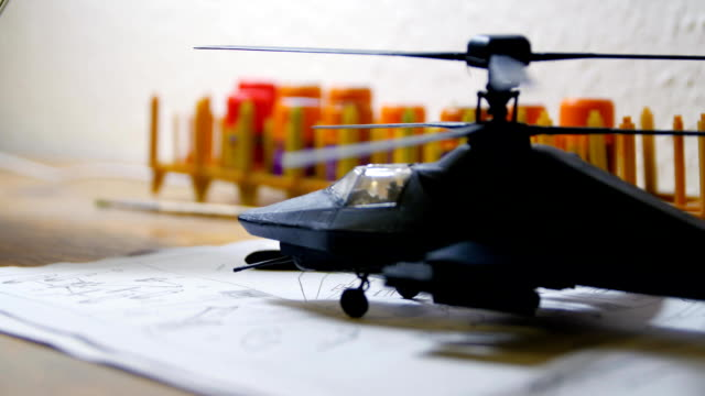 Toy Military Helicopter on wooden table. Small army helicopter hobby model toy on the table. Toy helicopter on the table video