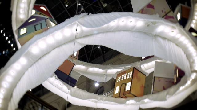 stockvideo's en b-roll-footage met speelgoed stad voor new year's en kerst decoraties in de winkelcentra, in het centrale deel. decoraties hangen plafond - christmas tree
