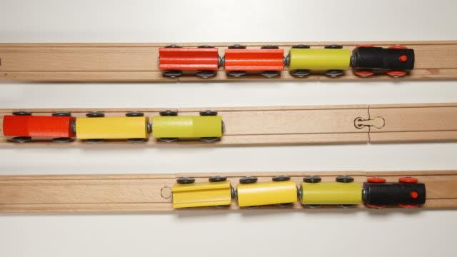 vídeos de stock e filmes b-roll de top view: toy wooden trains move on railways towards each other (stop motion) - reto descrição física