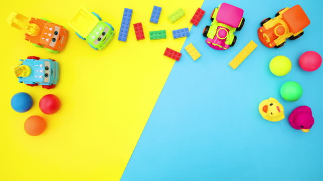 Toys for kids moving on blue and yellow background - Stop motion
