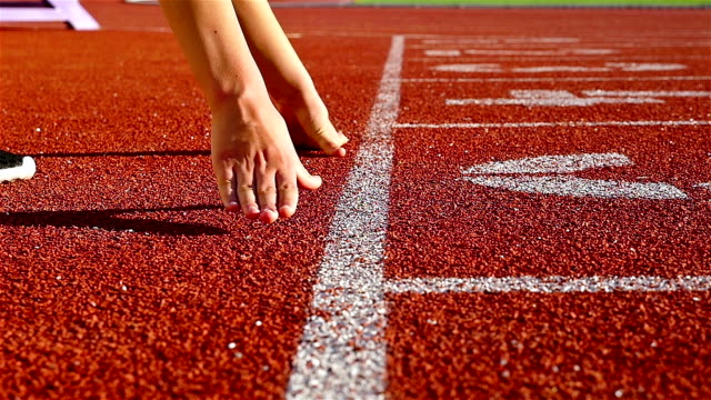 Track runner woman putting her hands at starting line, slow motion video