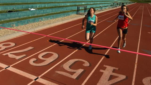 track runners at finish line, slow motion - tävlingsidrott bildbanksvideor och videomaterial från bakom kulisserna