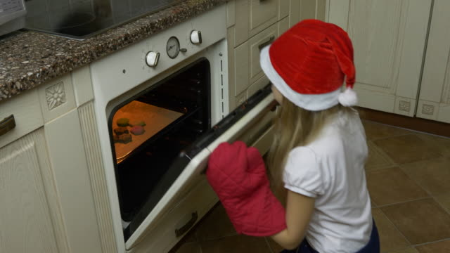 Track slide shot. Young girl claps hands and check cookies in oven. Girl bakes gingerbread cookie. Girl opens oven at kitchen and take out cookies for Christmas. Girl smiling and looking to camera. video