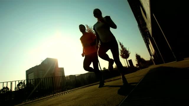 HD: Tracking A Couple Jogging On Sidewalk