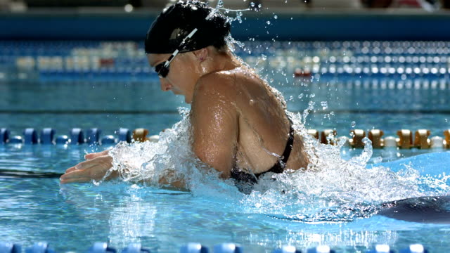 HD SLOW MOTION: Tracking A Woman Swimming Breaststroke HD1080p: Slow Motion Tracking shot of a young woman swimming breaststroke in the lap pool. swimming stock videos & royalty-free footage