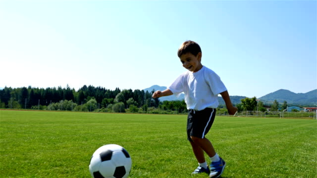 Tracking camera of a little 3 years old boy scoring a goal in a football field video