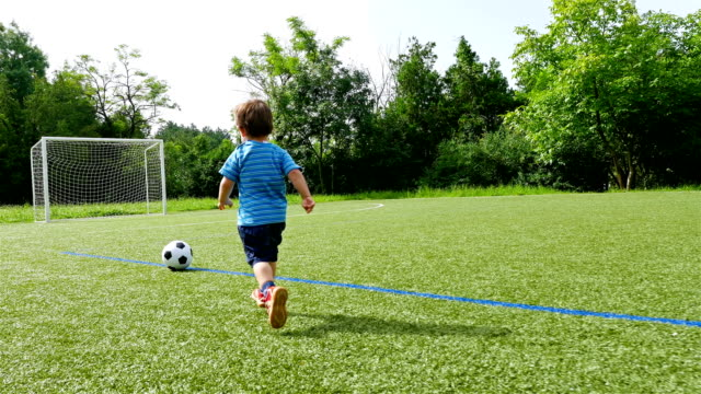 vídeos de stock e filmes b-roll de tracking camera of a little boy scoring a goal in football field - chutar