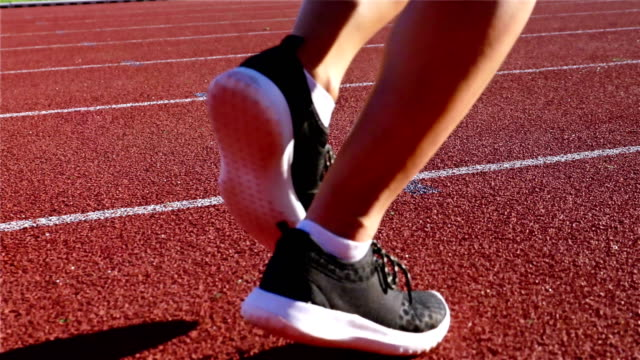 Tracking camera of the legs of a track runner athlete woman running in a line video