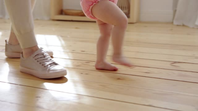 Tracking close-up shot of mother helping her barefoot baby daughter in pink bodysuit to make first steps at home Tracking close-up shot of mother helping her barefoot baby daughter in pink bodysuit to make first steps at home first occurrence stock videos & royalty-free footage