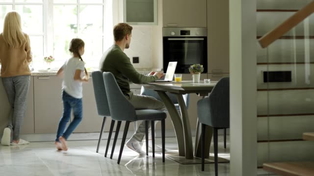 tracking left shot of middle aged man using laptop computer sitting at table in domestic kitchen. little daughter running downstairs to him, caring mother giving her glass of orange juice and kissing - family home video stock e b–roll