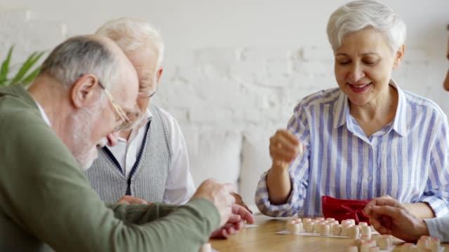 tracking medium shot av grupp fyra glada äldre människor, två män och två kvinnor, ha roligt sitter på bordet och spela bingo spel tillsammans i sjukhem - bingo bildbanksvideor och videomaterial från bakom kulisserna