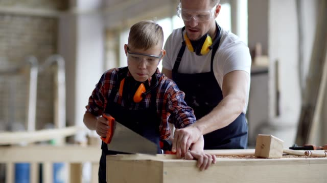 tracking medium shot of middle aged carpenter teaching son how to cut wooden plank with hand saw standing at workbench in carpentry shop, both wearing aprons and protective eyewear - narzędzie do pracy filmów i materiałów b-roll