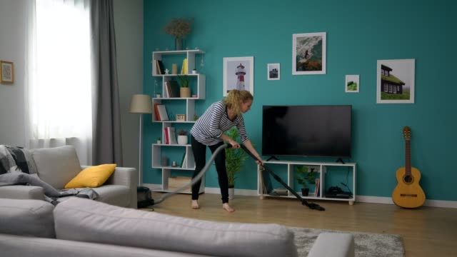 Tracking of young beautiful girl vacuuming her cozy apartment video