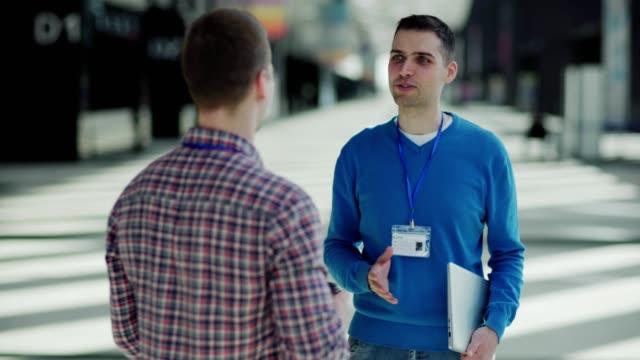 オフィスロビーでのイベント後に同僚と話すビジネスカンファレンスの出席者の右ショットを追跡します。二人の男がさよならに握手して立ち去る - メダル点の映像素材/bロール
