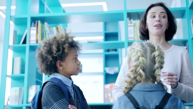 stockvideo's en b-roll-footage met tracking right shot van vrouwelijke leraar met vrolijke praten met de groep van drie elementaire studenten staande in de buurt boekenplanken in de schoolbibliotheek. planner en laptop computer in haar handen - literatuur