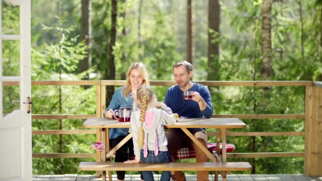 tracking right shot of happy family of three talking cheerfully while having breakfast at wooden table on country house balcony surrounded by green trees in sunny morning - tavolo legno video stock e b–roll