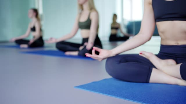 Tracking right shot of three unrecognizable barefoot women sitting in lotus position on yoga mats and doing group meditation with their hands on knees