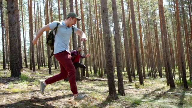 vídeos de stock e filmes b-roll de tracking right shot of two awfully scared young men with backpacks running through forest in slow motion fleeing from danger and screaming awfully terribly - fugir