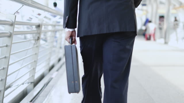 Tracking shot: Businessman holding briefcase and walking forward.