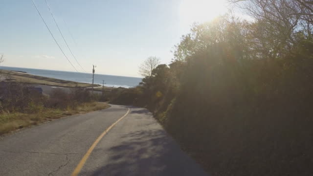 Tracking shot down a winding road, overlooking the ocean video