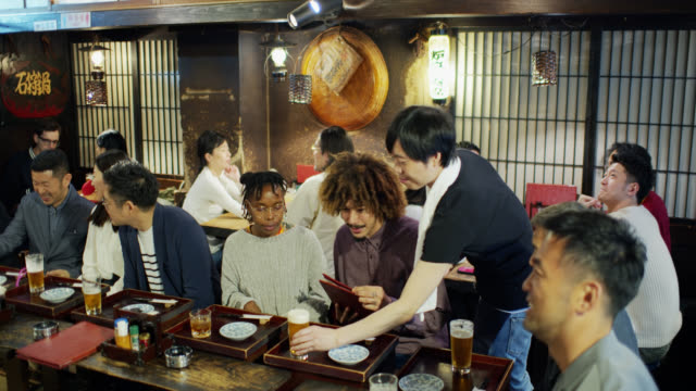tracking shot following waiter through crowded tokyo restaurant - bar lokal gastronomiczny filmów i materiałów b-roll