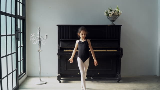 4K Tracking shot happy little child girl dancer in black leotard and ballet slipper shoes jumping and dancing contemporary ballet dance practice at vintage studio room. Young girl dancing in the room.