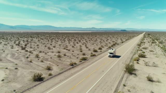 stockvideo's en b-roll-footage met tracking shot van een camper rijden door de mojave deser helemaal alleen - caravan