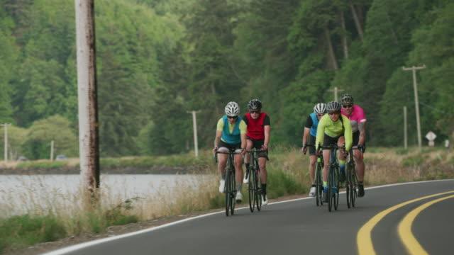 vidéos et rushes de travelling d'un groupe de cyclistes sur route de campagne. - moto sport