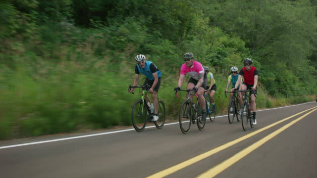 tracking shot of a group of cyclists on country road. - triatleta video stock e b–roll