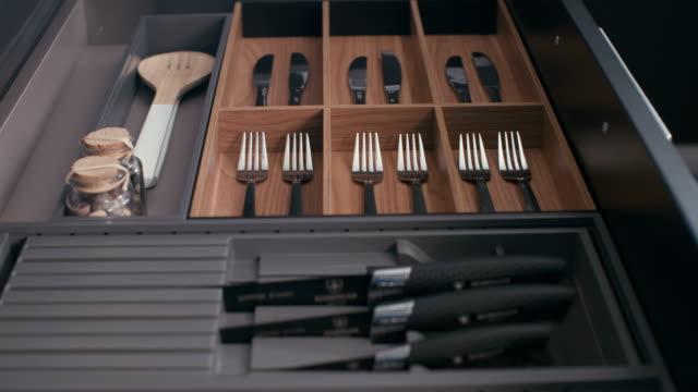 kamerafahrt von einem küchenschrank utensilien in einer luxusküche - teurer lebensstil stock-videos und b-roll-filmmaterial