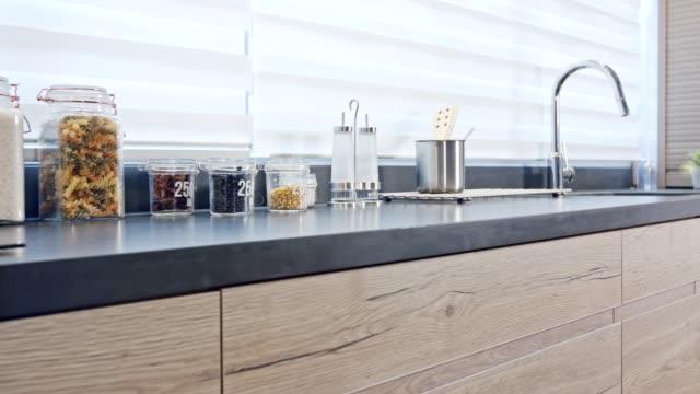 木製仕上げモダンなデザインの大きな高級キッチンのトラッキングショット - キッチンカウンター点の映像素材/bロール