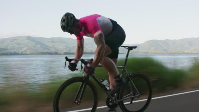 vidéos et rushes de travelling d'un mâle cycliste sur route de campagne. - moto sport