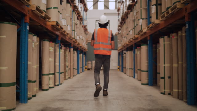 Tracking shot of a male worker in white hardhat and reflective jacket walking through the large stack of packages in warehouse