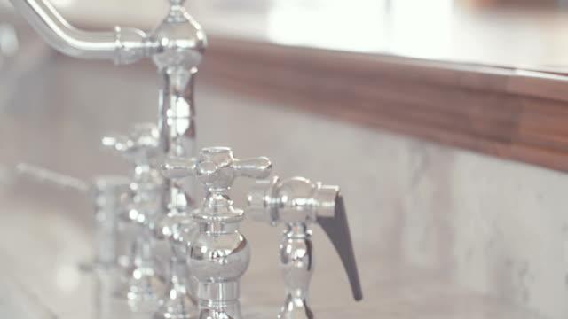 kamerafahrt von einem silbernen wasserhahn in einer luxusküche - teurer lebensstil stock-videos und b-roll-filmmaterial