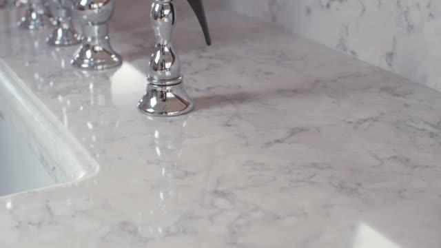 spårning skott av en silver kran i ett lyxigt kök - marble bildbanksvideor och videomaterial från bakom kulisserna
