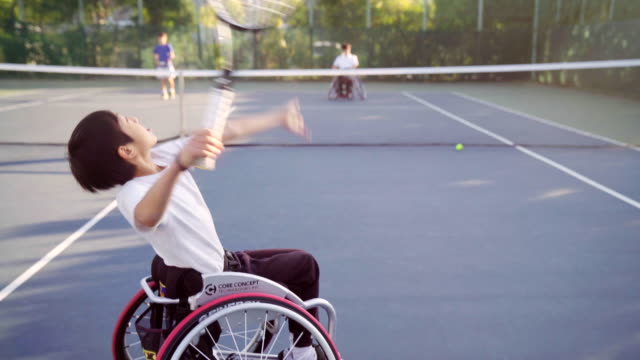 vídeos de stock e filmes b-roll de tracking shot of a teenage adaptive tennis player serving - capacidades diferentes